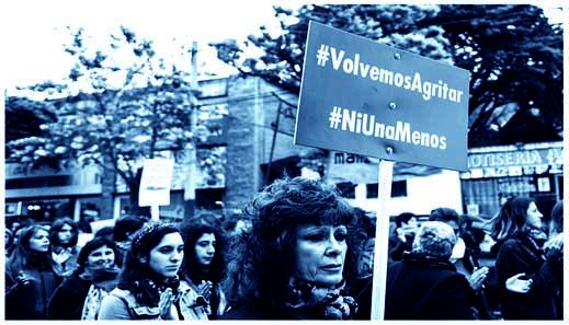 Foto einer Frauen Demonstration in Chile. Eine Frau im Vordergrund hält ein Schild mit dem Slogan Volvemos Agritar und NiUna Menos hoch